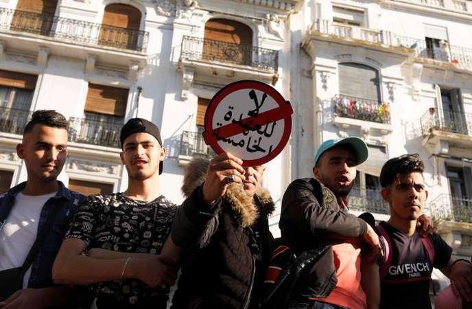 """A protester holds a sign that reads """"No to a fifth term"""" during the protest against President Abdelaziz Bouteflika's plan to extend his 20-year rule by seeking a fifth term in April elections, in Algiers"""